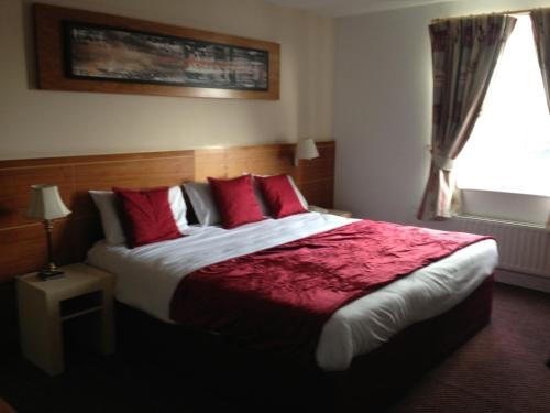 A bed or beds in a room at Ashbourne House Hotel