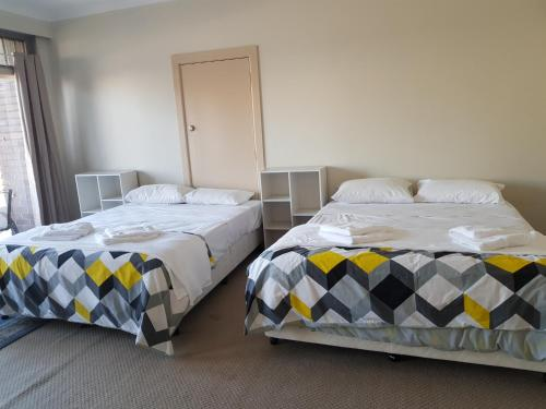 A bed or beds in a room at Orange Grove Hotel