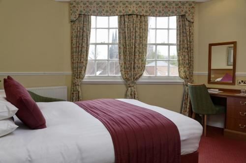 A bed or beds in a room at Best Western Lichfield City Centre The George Hotel