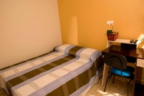 A bed or beds in a room at Orquídea Hotel