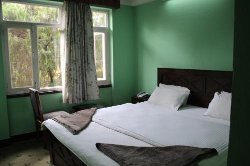 A bed or beds in a room at Mount Annapurna Guest House