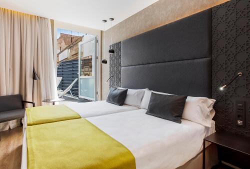 A bed or beds in a room at Catalonia Giralda