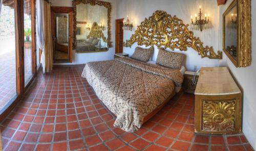 A bed or beds in a room at Posada de la Mision, Hotel Museo y Jardin