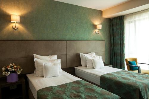 Un pat sau paturi într-o cameră la Victoria Bulevard Hotel