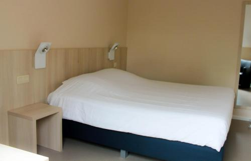A bed or beds in a room at La Couronne