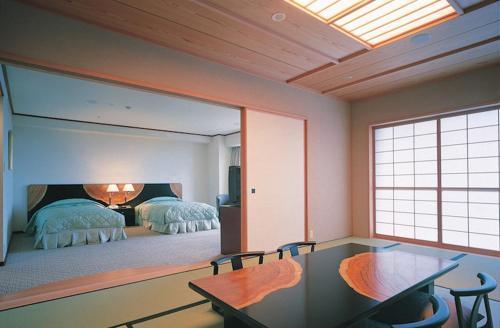 A bed or beds in a room at Yakushima Iwasaki Hotel