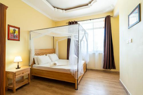 A bed or beds in a room at Rayan Apartments & Safaris