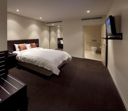 A bed or beds in a room at Atlantis Hotel Melbourne