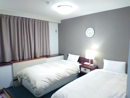 A bed or beds in a room at Hotel Crown Hills Imabari