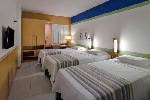 A bed or beds in a room at Verdegreen Hotel