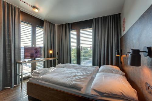 A bed or beds in a room at MEININGER Hotel Berlin Tiergarten