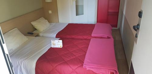A bed or beds in a room at Premiere Classe Deauville Touques