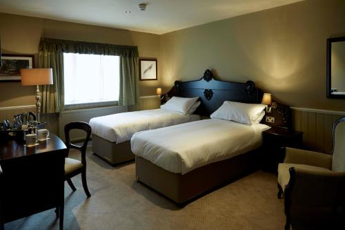 A bed or beds in a room at The Golden Pheasant