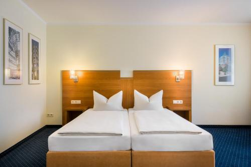 A bed or beds in a room at acora Hotel und Wohnen Bochum