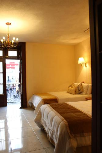 A bed or beds in a room at Hotel Insurgente Allende