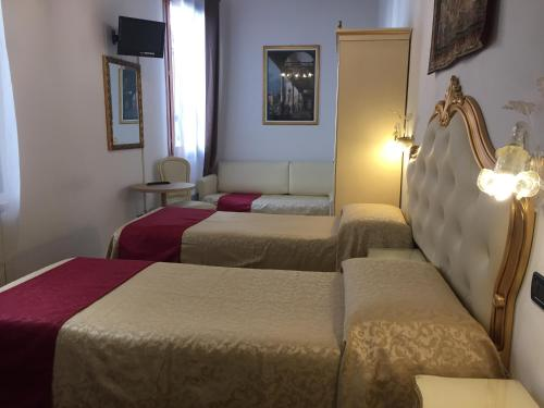 A bed or beds in a room at Locanda SS. Giovanni e Paolo