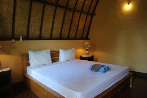 A bed or beds in a room at Gili Cemara Bungalows