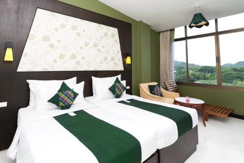 A bed or beds in a room at River Kwai Hotel