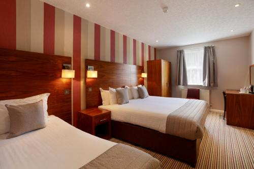 A bed or beds in a room at The Victoria Hotel