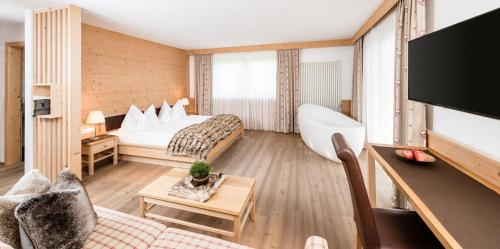 A bed or beds in a room at Boutique Hotel Nives - Luxury & Design in the Dolomites