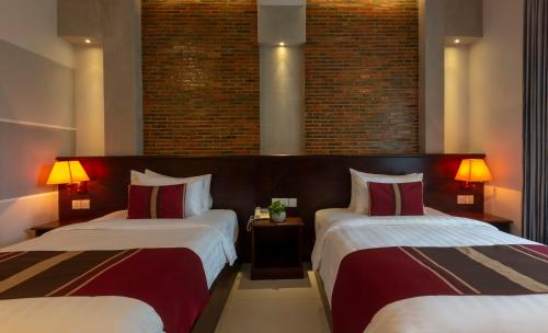 A bed or beds in a room at Sovanna Hotel