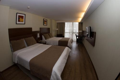 A bed or beds in a room at Howard Johnson La Cañada Hotel & Suites