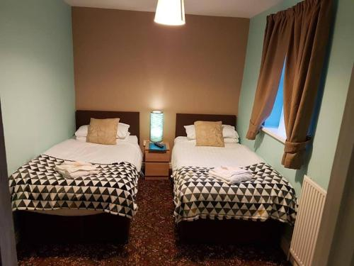 A bed or beds in a room at Denville Hotel