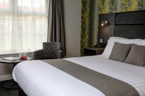 A bed or beds in a room at Allerton Court Hotel