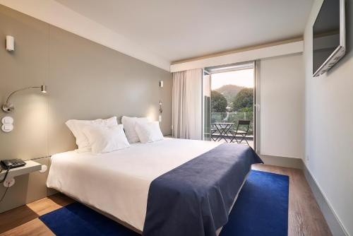 A bed or beds in a room at Ribeira Collection Hotel - Piamonte Hotels
