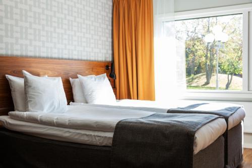 Säng eller sängar i ett rum på Rönneberga Konferens