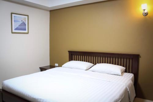 A bed or beds in a room at Yellow House Rayong