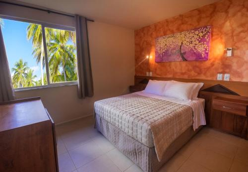 A bed or beds in a room at Village Paraíso Tropical