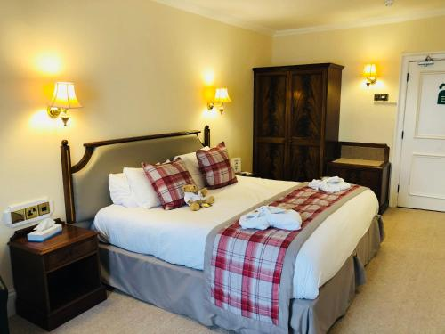 A bed or beds in a room at Dryburgh Abbey Hotel