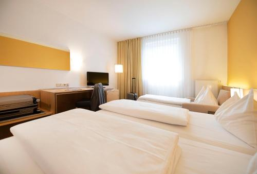 A bed or beds in a room at HEINHOTEL Vienna Airport