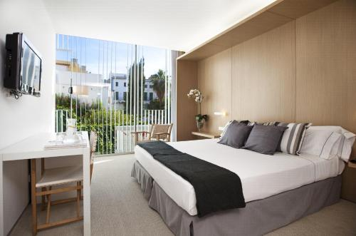 A bed or beds in a room at Alenti Sitges Hotel & Restaurant