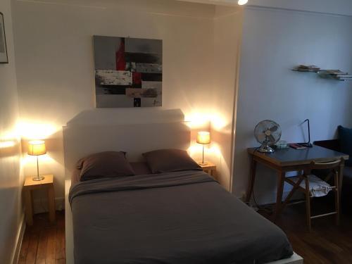 Postel nebo postele na pokoji v ubytování Louvre Studio
