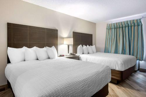 A bed or beds in a room at Clarion Inn & Suites Kissimmee-Lake Buena Vista South