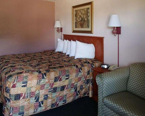 A bed or beds in a room at Rodeway Inn Leesburg Chain of Lakes