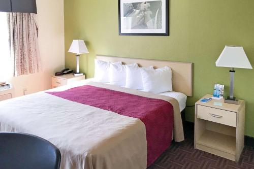 A bed or beds in a room at Rodeway Inn Gloucester City