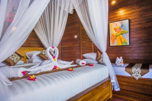 A bed or beds in a room at Tatak Bunut villa