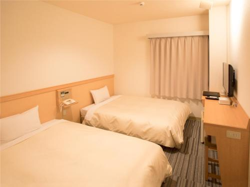 A bed or beds in a room at Premier Hotel Cabin Matsumoto