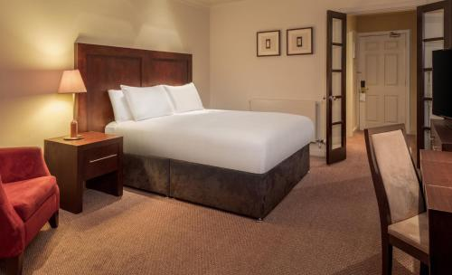 A bed or beds in a room at Doubletree By Hilton Glasgow Westerwood Spa & Golf Resort