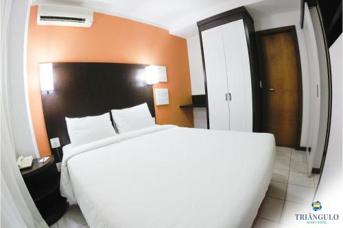A bed or beds in a room at Triângulo Apart Hotel
