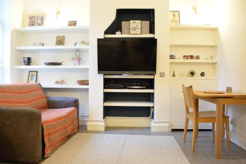 A television and/or entertainment center at 2 Bedroom Property in the Heart of Angel