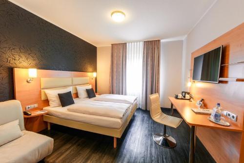 A bed or beds in a room at Best Western Plaza Hotel Stuttgart-Filderstadt