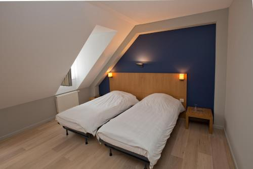 A bed or beds in a room at Hotel De Zalm