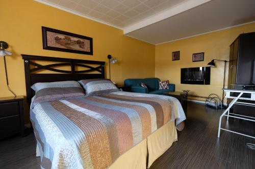 A bed or beds in a room at Motel Canadien