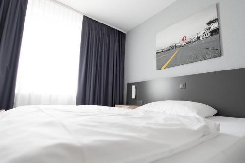 Ein Bett oder Betten in einem Zimmer der Unterkunft Airporthotel Grenchen