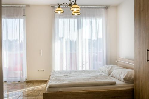 A bed or beds in a room at Luxury Apartment Hotel Siófok