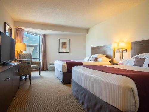 A bed or beds in a room at Ramada by Wyndham Kamloops